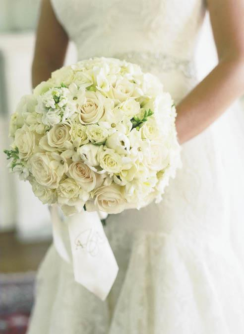 SPHERE OF INFLUENCE: Ashley carried a bouquet by Soirée of white roses, peonies, spring tulips, lisianthus, and stephanotis. A monogrammed silk ribbon garnished the bundle