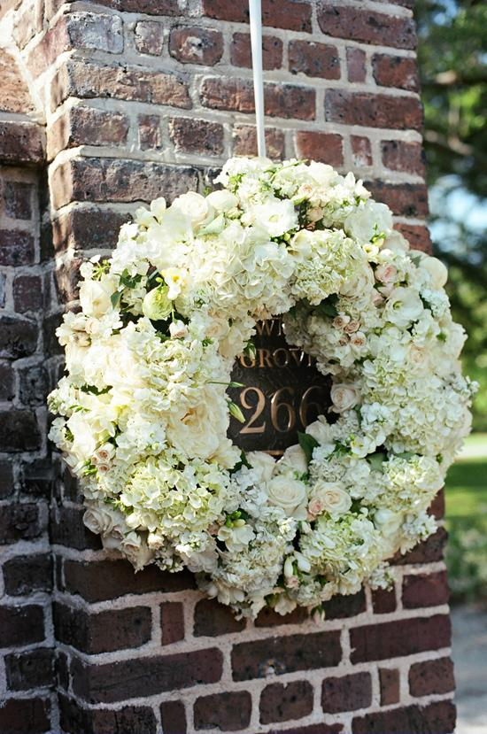 A WELCOMING WREATH: The Soirée team stuck roses, spray roses, peonies, lisianthus, stephanotis, spring tulips, and stock flowers into rings of flower foam to dress up the brick entrance of Lowndes Grove.