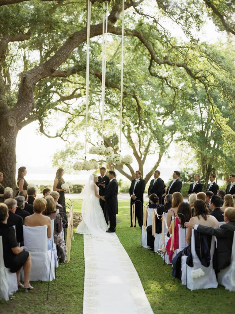 "HANGING GARDEN: Chandeliers adorned with roses, peonies, lisianthus, and tulips were hung with champagne-hued ribbon to frame the open-air ""altar."""