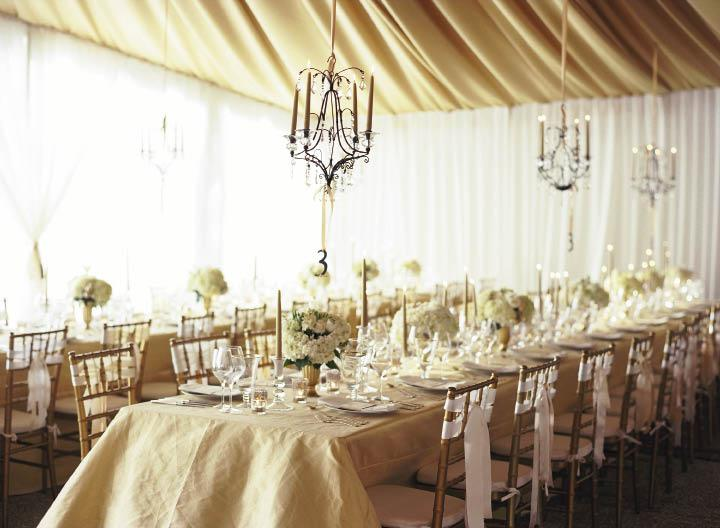 GET THE GLOW: Sheer white curtains  allowed natural light to fill the tent; when the sun set, candles and flame-lit  chandeliers brightened the space.