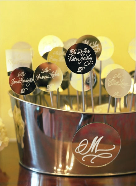 MIRROR, MIRROR: For an airy effect, table assignments were calligraphed onto mirrored circles, which Soirée attached to silver sticks and presented in metal baskets.