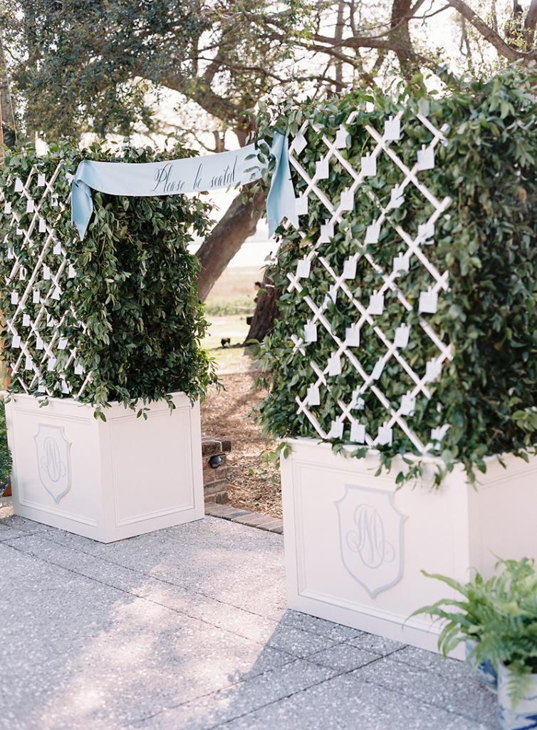 """A silk banner in French blue with white lettering read, """"Please be seated"""" and beckoned the 100 guests from the cocktail party to the reception. Escort cards were tucked into the boxwood entrance that was made especially for the evening."""