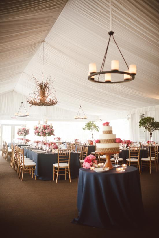 BRANCH OUT: To bring the woodland motif indoors beneath the tent, Gathering Floral + Event Design hung a statement chandelier made of branches.