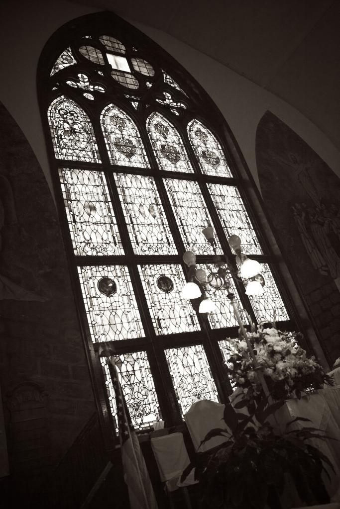 SACRED BEAUTY: An exquisite floor to ceiling stained glass window, located directly behind the altar, filled the church with lots of natural light for the afternoon ceremony.