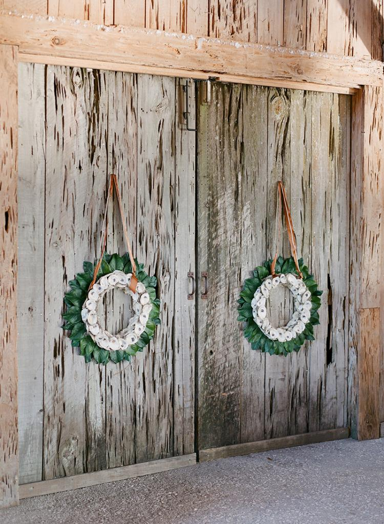 Homemade magnolia leaf and oyster shell wreaths hung from the dock doors with the same ribbon the bridesmaids wore as sashes.