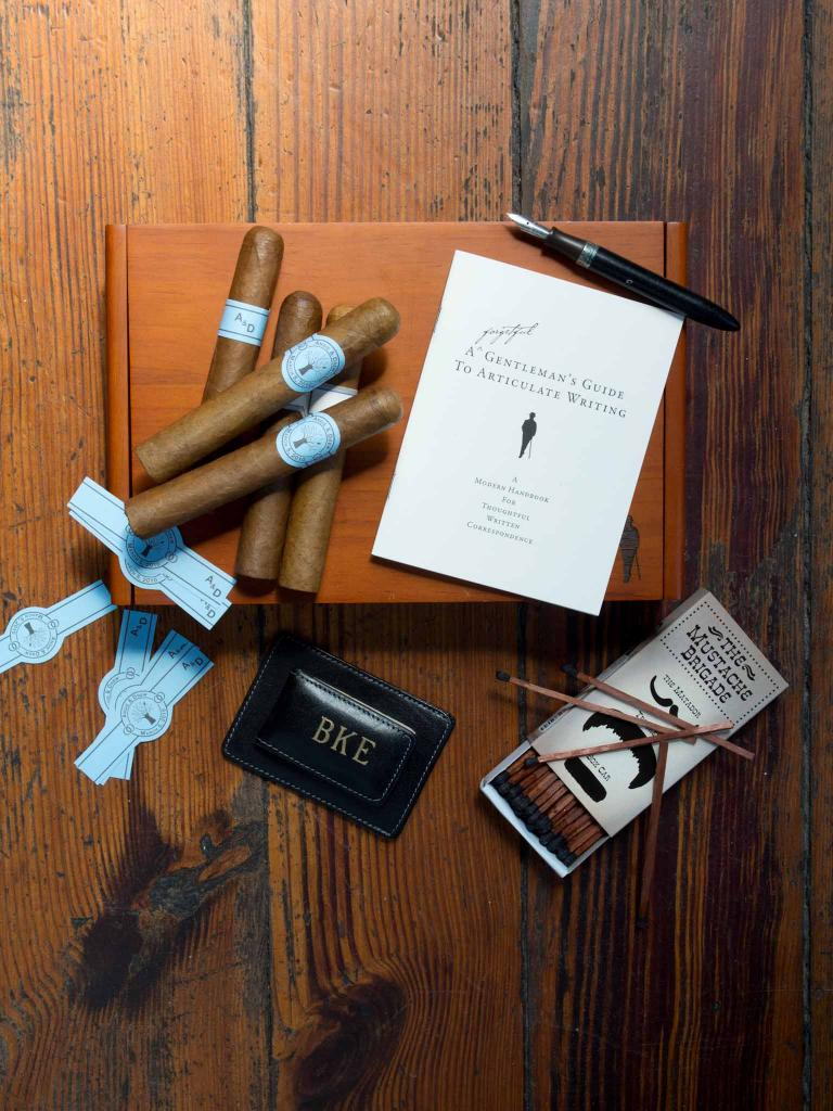 MANLY THINGS: Hand-rolled cigars with custom bands from Coastal Cigars. Moustache matches, pen, and Forgetful Gentlemen stationery from Ooh! Events. Money clip from Croghan's Jewel Box.