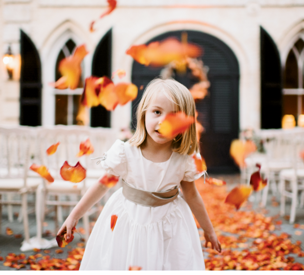 To harken fall foliage, Loluma gave this downtown wedding a fiery runner of ombré orange rose petals that the flower girl couldn't resist. (Photograph by Sean Money + Elizabeth Fay)