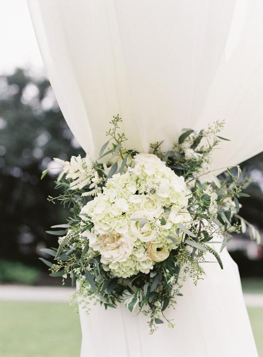 Curtain tie-backs were punctuated with bundles of garden roses, hydrangeas, and seeded  eucalyptus from Sarah York Grimshaw Designs.