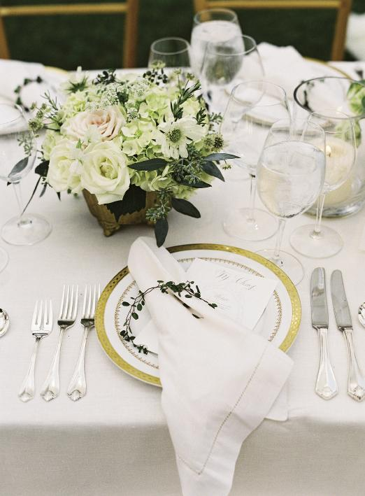 "Snyder Event Rentals' ""Imperial Gold"" china lent a formal tone to place settings that were finished with the company's ""King James"" silver-plated flatware and hemstitched linen napkins accented with fresh garlands of angel vine."