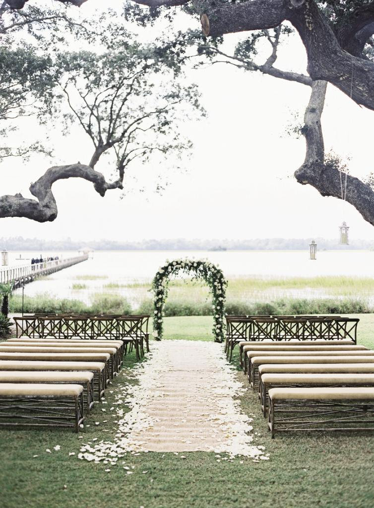 Easton Events dressed the ceremony in their hallmark elegant style, with an arbor of softly draping greens and fragrant white blooms by Sara York Grimshaw Designs; a seagrass runner edged with fresh rose petals; and benches bearing natural-hued linen cushions from Snyder Event Rentals.