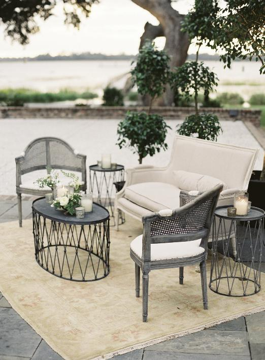 Easton Events created outdoor lounges with topiaries, Oriental rugs, cane-backed chairs from Snyder Event Rentals, linen settees, and wire side tables.