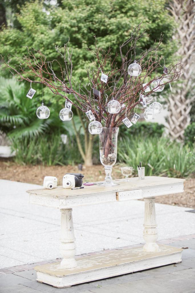 Guests took selfies with instant cameras and hung them from branches lit by crystal  votives. Later, the couple filed the images away in a keepsake album.