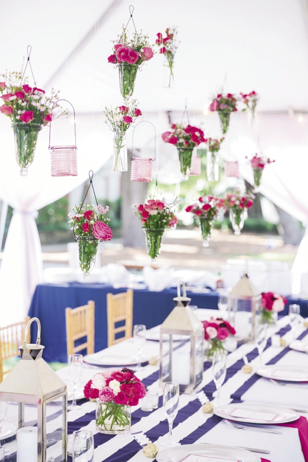 CLOSE QUARTERS: An airy cloud of spray roses, waxflower, ranunculus, and garden roses floated over the dining table in suspended glass vases.