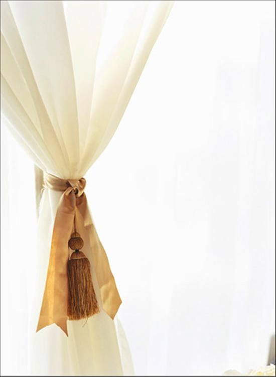 SEEING DOUBLE: Décor from the ceremony was tied into the reception—panels of sheer fabric were held back by silk ribbon accented with tassels.