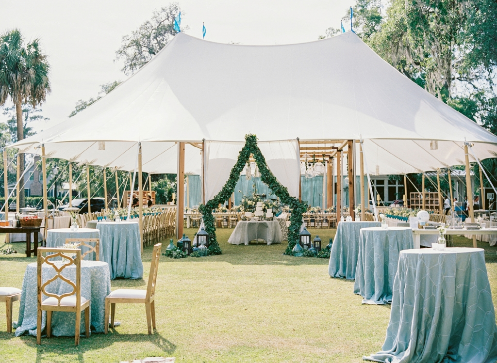 "Mere steps from the chapel, the sailcloth tent on the Village Green beckoned guests to celebrate al fresco. A gospel choir serenaded the couple and their guests with ""You Are My Sunshine"" as they strolled into the party."