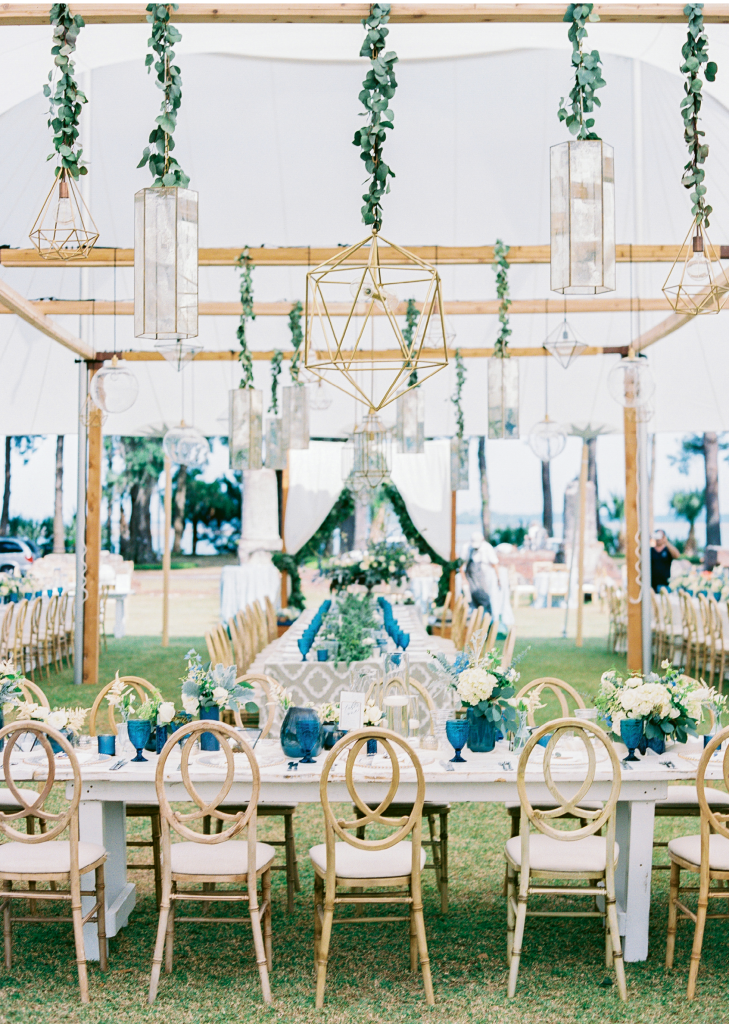 "Even without side panels, a tent can define a space as with this outdoor ""dining room."" Look closely to see the patterned runners on the tables; those sport the same design as the butler card tiles in the shot at left. As for the blue glassware, Carla fell for them long before she was engaged. When wedding planning kicked off, she tracked them down and bought 250 for the Big Day. Afterward, she divvied them up between her parents, her sister, and herself."