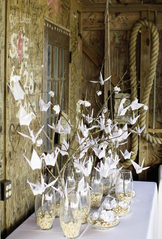 FLOCK TOGETHER: Paper cranes and flowers hung off branches rooted in stone-weighted vases.