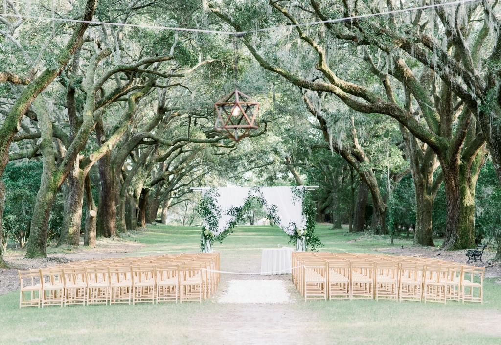 Shade from towering oak trees kept guests  cool during the alfresco ceremony.  <i>Image Aaron & Jillian Photography</i>