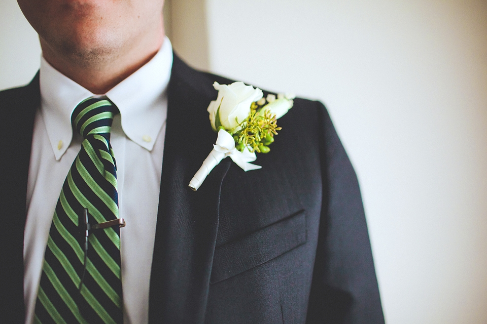 FRESH PICK: For the groom's boutonniere, Loluma arranged a white rose with simple greens complementing his green and navy striped tie.