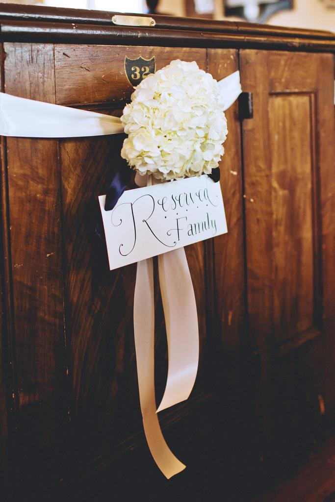 FAMILY FIRST: A large white hydrangea tied with ribbon reserved the front pew for members of the couple's family.