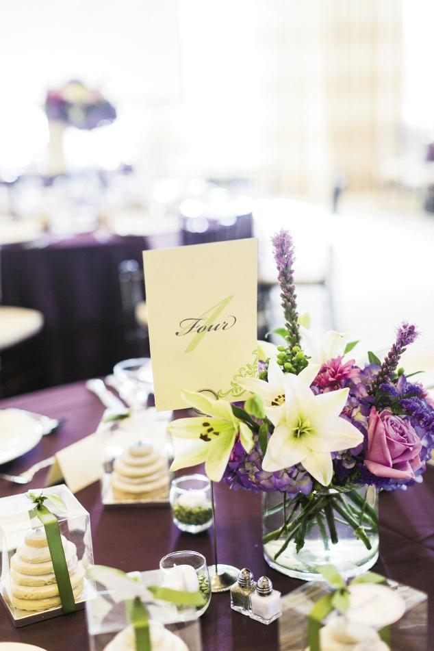 "WHAT A TREAT: Tables covered in bold purple linens were topped with purple stock, fuchsia roses, purple blazing star, and white lilies by OK Florist. Erica's mother, aunt, and cousins made miniature ""cake"" favors from stacked cookies they iced together."