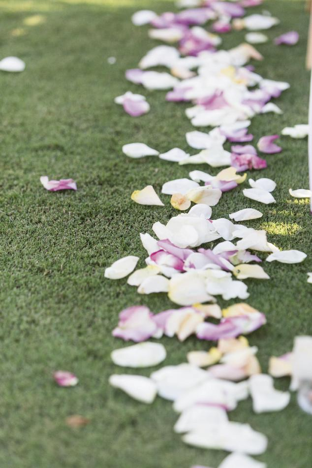 FLOWER POWER: The greens at Daniel Island Club are so pristine, a simple cascade of white and pale purple rose petals was more than enough to dress the aisle.