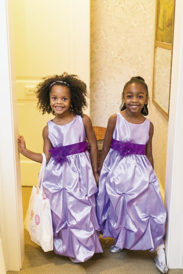 "GIRL TALK: Flower girls Sydney and Trinity's lilac dresses kicked off the purple parade. They had a blast, says Erica, ""But Sydney barely made it down the aisle since she dropped all of her rose petals before she hit the guest chairs!"""