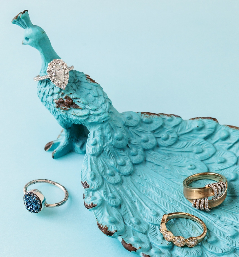Blue druzy and sterling silver ring ($16.75 from Porter Conrad). Forevermark's diamond and white gold ring (1.875 total cts.; $13,999 from REEDS Jewelers). Diamond and gold band ($1,860 from Croghan's Jewel Box). Gabriel & Co.'s diamond and gold ring ($1,395 from Polly's Fine Jewelry). Peacock holder ($12 from Hobby Lobby).   <i>Photograph Gayle Brooker</i>