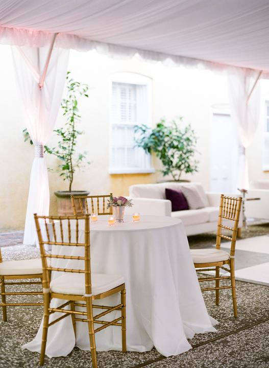 HOT SEAT: Metallic gold dining chairs stood out against white linens and gauzy tent fabric.
