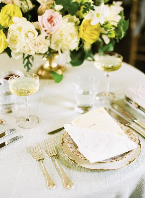 "IN THE FOLD: Kristin Newman Designs tucked the couple's ""Book of Love"" menu into a folded Battenberg lace napkin and placed it atop hand-selected heirloom china. Etched champagne coupes—a shape  originally designed for English aristocrats—finished the look on the sweetheart table."
