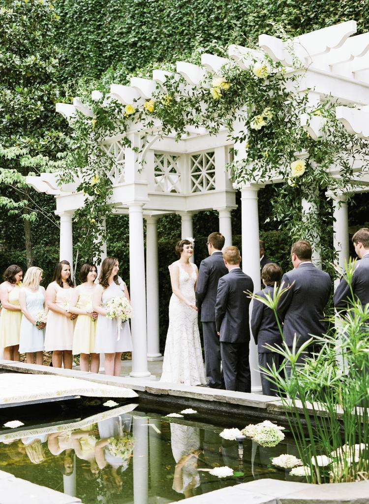 NEW HEIGHTS: Gathering Events turned the  William Aiken House's arbor  into a garden trellis with a  meandering vine of smilax and  yellow peonies—the bride's favorite flower. Hydrangea blooms floated in the lily pond, which was spanned with a temporary bridge covered with a damask-style runner.