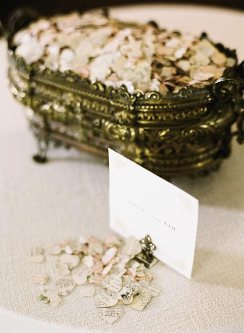 WORDS OF WISDOM: Flower petals and heart-shaped confetti punched from pages of books rained down on the couple as they left the reception.