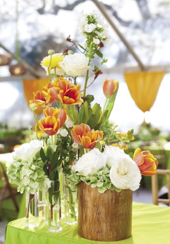APRIL SHOWERS: Blossoms Events filled glass beakers and wooden cylinders with garden roses, hydrangea, ranunculus, tulips, and more.