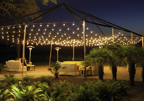 LATE NIGHT TALK SHOW: Palmetto trees, torches, and string lights formed an intimate outdoor setting for conversation.
