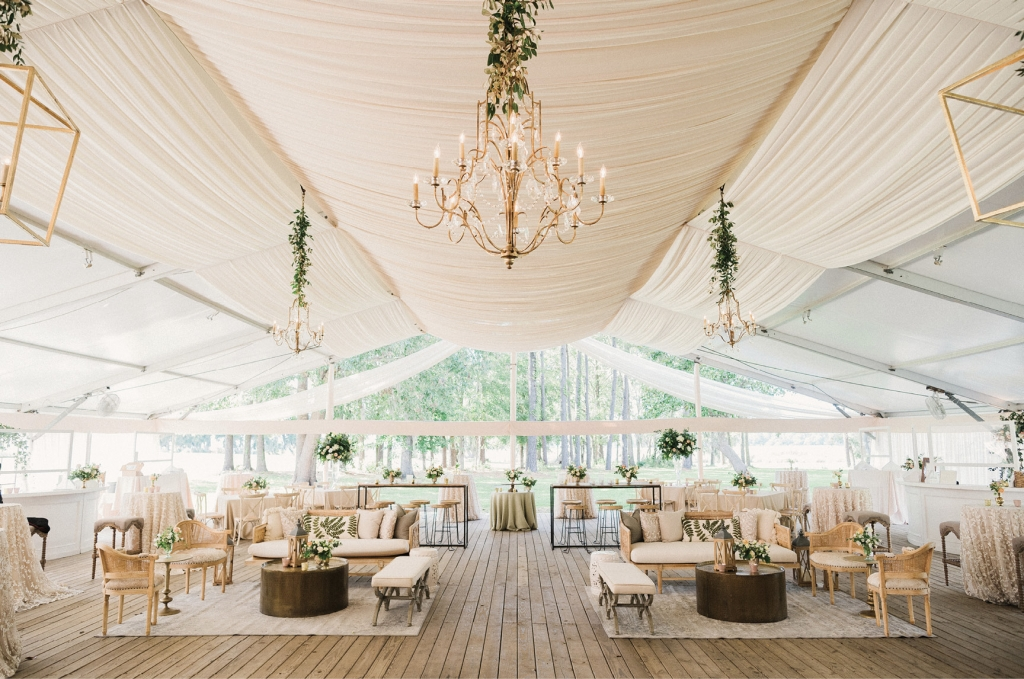 In the reception tent, elegant draping and a mix of hanging lanterns and chandeliers helped achieve the semi-rustic and glam aesthetic. The various textures, neutral hues amid pops of greenery, and a harmonious arrangement of traditional sit-down tables and lounge furniture created a breathtaking and welcoming environment.