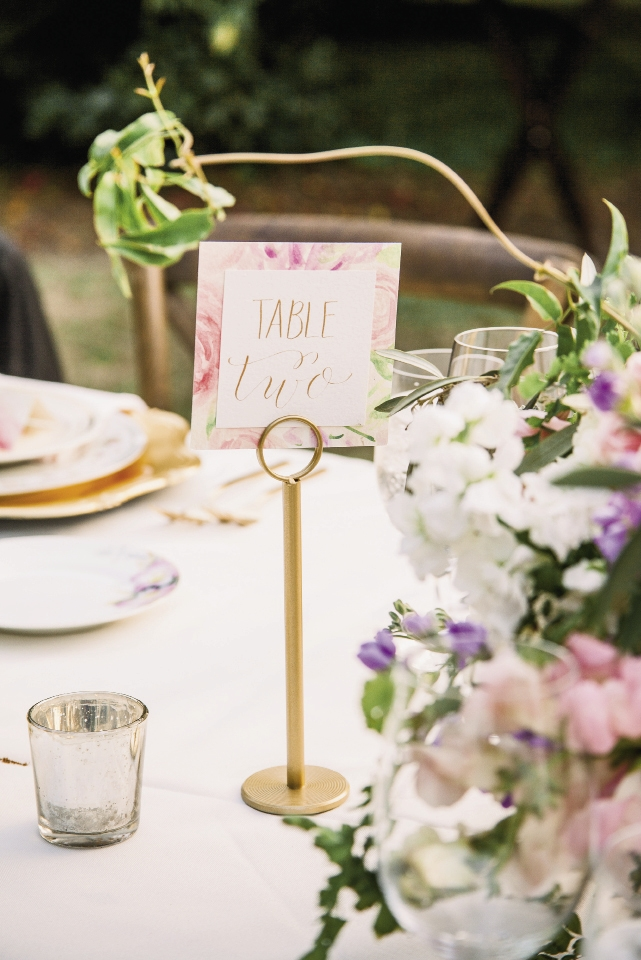 Table numbers riffed off the invitation suite while mercury glass votives added tabletop luster even before dark fell.