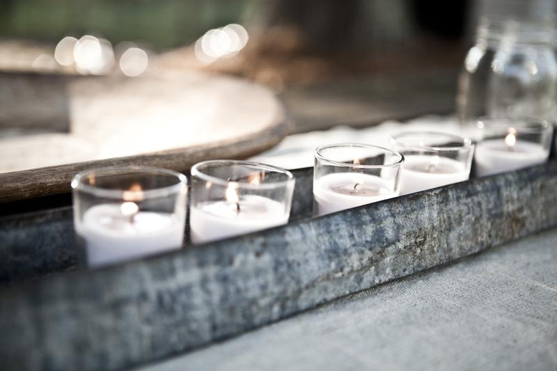 "LIGHT THE WAY: Ashley says, ""I'm a sucker for some soft, romantic lighting."" She sprinkled simple votive candles throughout the décor—here, lining them within a rustic metal vessel."