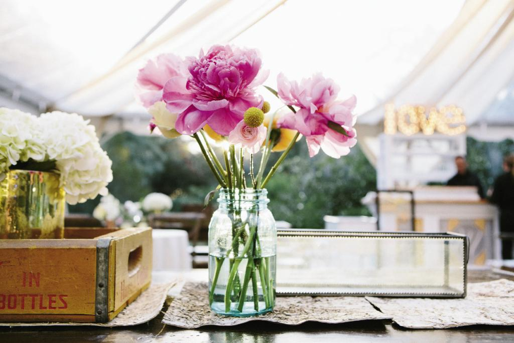 "LUCKY BREAK: ""The fuchsia peonies were a real surprise,"" says Anne Dabney of stems, ""they're not easy to get in November, so Sarah was beyond thrilled to see them."" Arrangements spilled from Ball jars placed atop moss table runners."