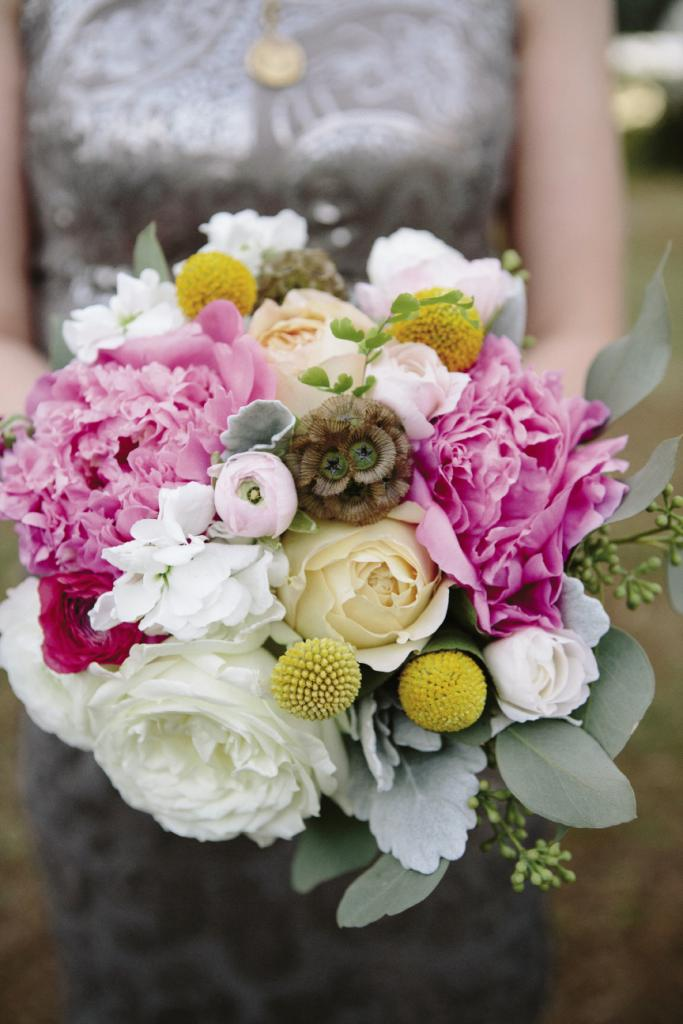 COPY CAT: Embedded among roses and ranunculus, earthy scabiosa in bridesmaids' bouquets echoed the groomsmen's boutonnieres.