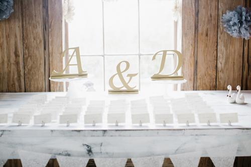 CRAFT CORNER: Lift a simple escort card display with natural wooden letters—found in any craft store—in the couple's monogram.