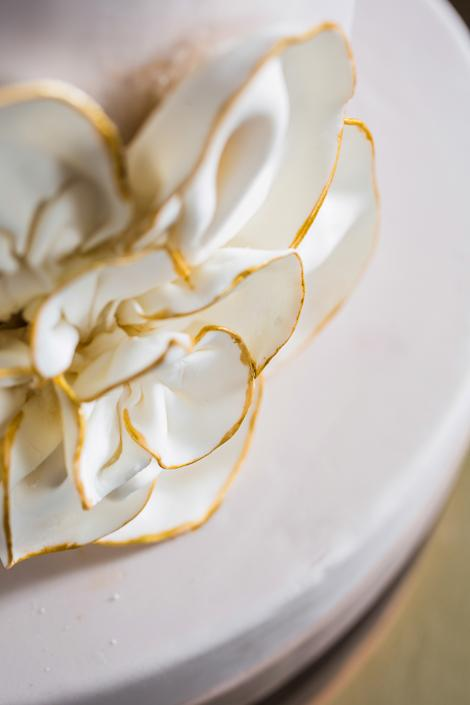 MIDAS TOUCH: Outlining the fondant flower in gold tied the cake back to the myriad gold accents in the rest of the setting.