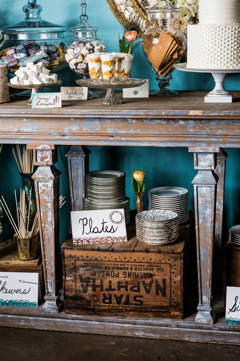 DOUBLE DECKER: Make full use of space and stock lower shelves with more goodies or necessities, like these serving plates. Call attention to tucked away items with signage to gently guide guests.