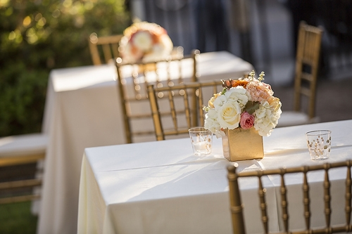 LOW PROFILE: Be mindful of conversation when planning your reception centerpieces. These gold boxes with short stems of roses and hydrangeas in the wedding's hues add impact while being practically sized.