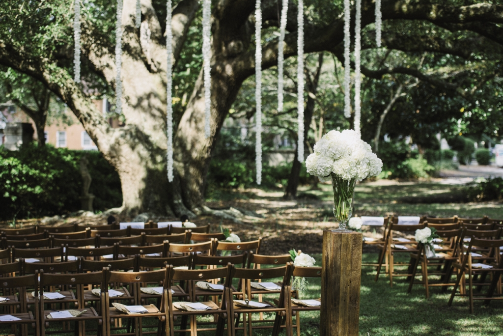 SUMMER WHITES: Julie wanted to enhance Lowndes Grove's natural beauty with only white flowers, so A Charleston Bride and florist Tiger Lily Weddings decorated the ceremony with simple, lush hydrangea arrangements and hung flower streamers from the trees to form the altar space.