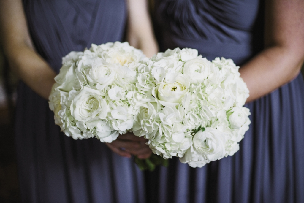 IN HAND: All-white bouquets of hydrangeas, garden roses, and ranunculus by Gayla Harvey of Tiger Lily Weddings offset the bridesmaids' navy dresses.