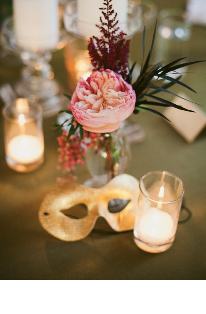 As a subtle nod to Halloween, table  assignments were attached to golden masks, which guests donned for a masqueraded beachfront cocktail hour. (Image by Juliet Elizabeth Photography)