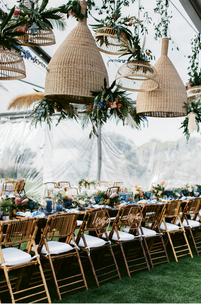 The extra large rattan shades over the head table answered the couple's request for a laid-back coastal vibe.