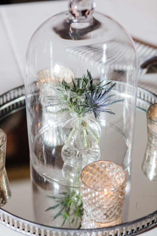 UNDER COVER: Turn a simple flower (like this thistle) and budvase into a curiosity centerpiece when you cover it with a glass cloche. One other trick? Placing it atop a mirrored tray doubles the volume and gives the illusion of centerpiece larger than life.