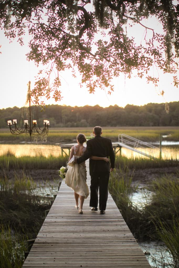 LET'S WALK: The newlyweds took a sunset stroll down the dock. Behind them dangled RiverOaks' trademark item—a rustic chandelier draped in Spanish moss.