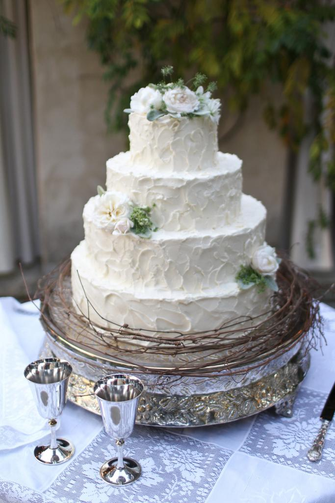 A TIER-FUL SIGHT: Real flowers and a skirt of thin sticks tied the cake into the rest of the reception décor.
